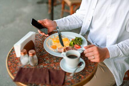 Hombre que usa el teléfono móvil mientras está en el café
