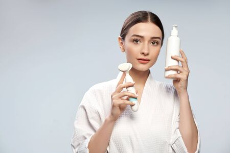 Beautiful girl holding bottle of cosmetic cream and pore cleansing brush