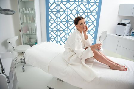 Happy lady with round mirror on massage table