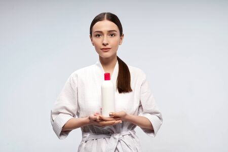 Beautiful young woman holding white bottle of cosmetic cream