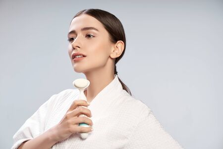 Attractive young woman in white bathrobe holding pore cleansing brush
