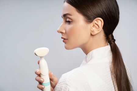 Charming young woman holding pore cleansing brush