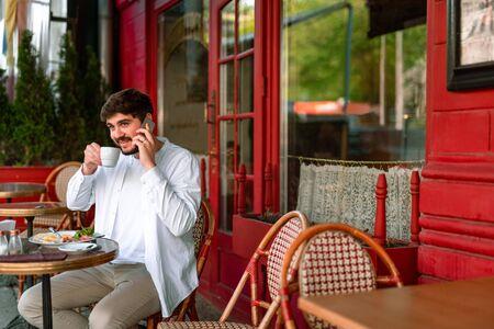 Happy man enjoying tea in cafe outdoors