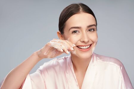 Joyful young woman washing face with foaming cleanser