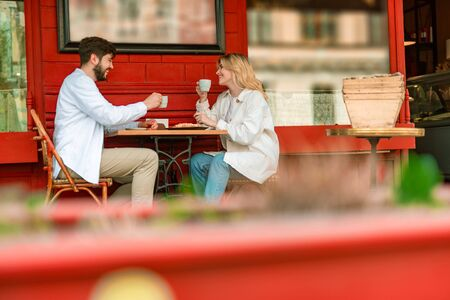 Happy young couple having date in outdoor cafe Stock Photo