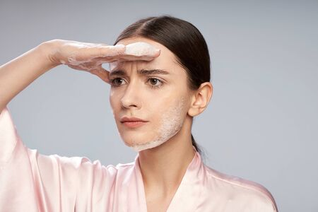 Beautiful girl with purifying foam on face keeping hand on forehead