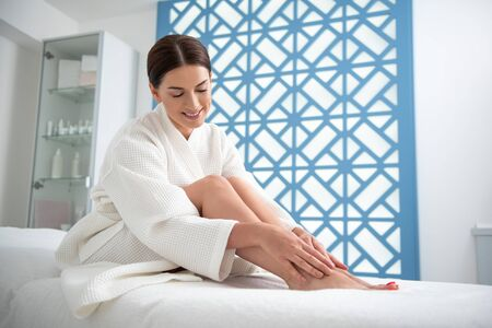 Smiling pretty lady sitting on massage couch