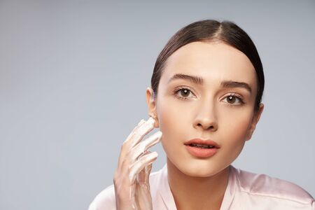 Attractive young woman planning to wash face with foaming cleanser