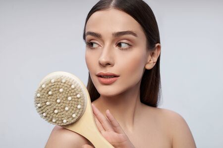 Attractive young woman with massage brush standing against white background