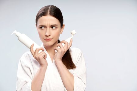Pretty girl holding bottle of cosmetic cream and pore cleansing brush