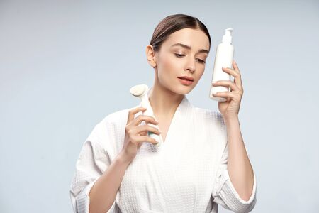 Attractive young lady holding bottle of cosmetic cream and pore cleansing brush
