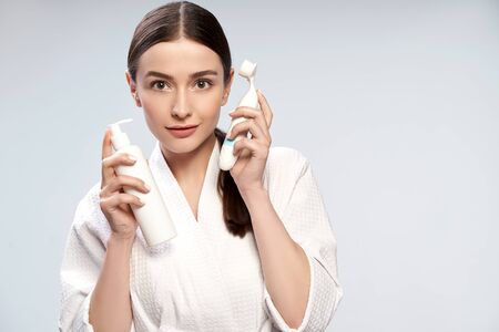 Beautiful young woman holding bottle of cosmetic cream and pore cleansing brush