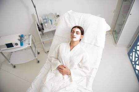 Top view female resting on couch with face mask