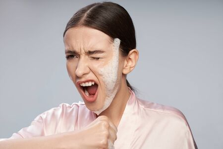 Beautiful girl with purifying foam on face screaming