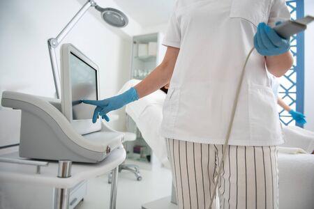 Close up lady therapist adjust suprasonic device