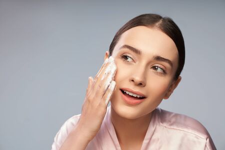 Attractive young woman washing face with foaming cleanser