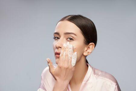 Belle jeune femme se lavant le visage avec un nettoyant moussant