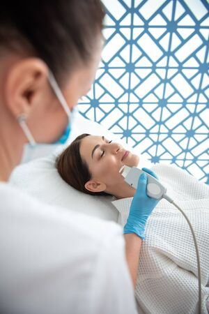 Young lady on suprasonic beauty procedure of face