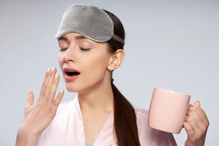 Tired young woman in sleeping mask holding cup of coffee and yawning