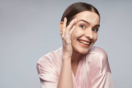 Cheerful cute girl washing face with foaming cleanser