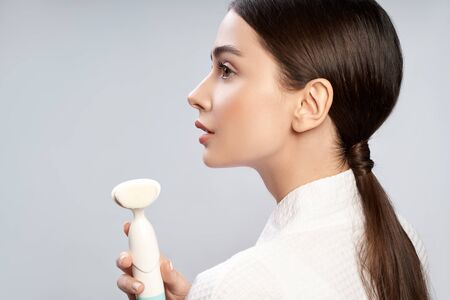 Gorgeous young woman holding pore cleansing brush