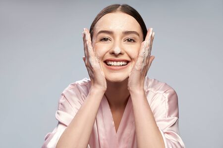 Cheerful pretty girl washing face with foaming cleanser