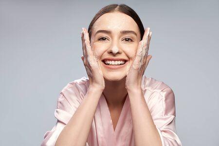 Vrolijk mooi meisje dat gezicht wast met schuimende reiniger Stockfoto