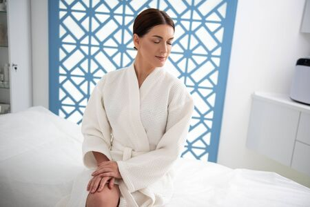 Lady with closing eyes sitting on massage table