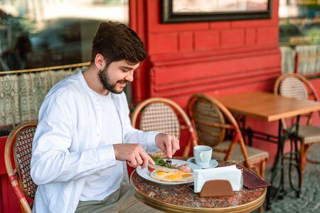 Glimlachende jonge man aan het ontbijt op terras Stockfoto