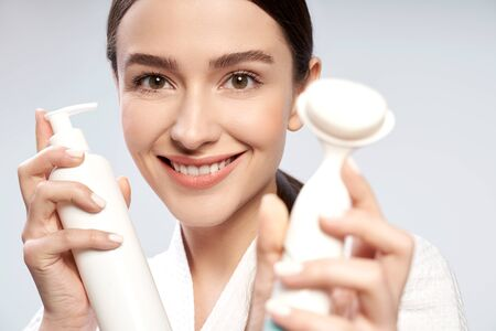 Joyful young woman holding bottle of cosmetic cream and pore cleansing brush 版權商用圖片