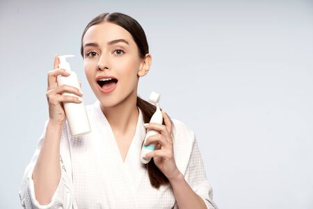 Charming young woman holding bottle of cosmetic cream and pore cleansing brush
