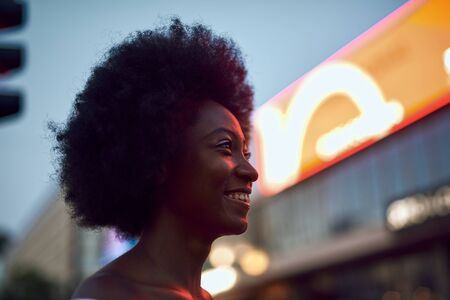 Pretty afro-american lady looking away and smiling outdoors Stockfoto