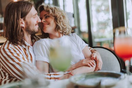 Beautiful happy couple cuddling while having date in cafe