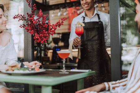 Handsome bartender serving cocktail to visitors in outdoor cafe
