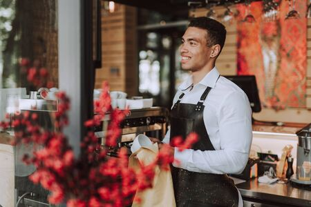 Handsome barman wiping white cup with cleaning cloth Reklamní fotografie