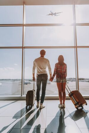 Man and woman are standing with suitcases at airport window. They are tenderly hand-holding and watching plane flying in sky Imagens