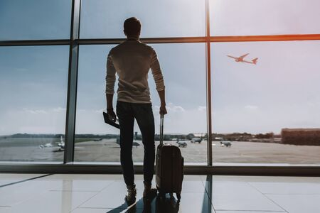 Guy is standing near big window at airport. He is looking outside and observing transport. Copy space in right side Imagens
