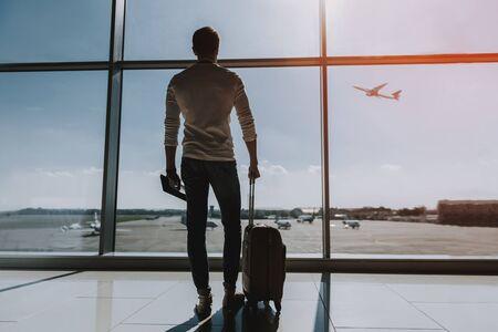 Kerl steht in der Nähe eines großen Fensters am Flughafen. Er schaut nach draußen und beobachtet den Verkehr. Kopieren Sie Platz auf der rechten Seite Standard-Bild