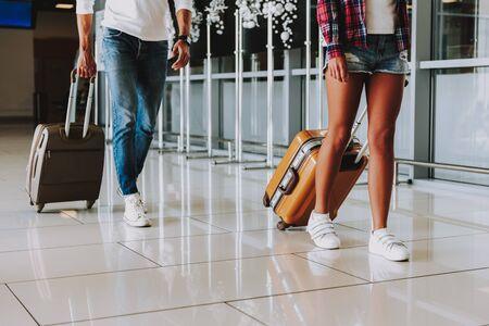 남자와 여자는 공항에서 걷는 동안 짐을 나르고 있습니다. 그들은 비행기로 여행에서 돌아오고 있습니다