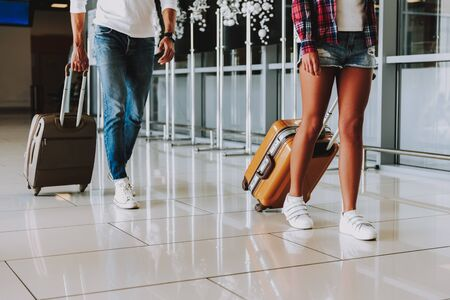 L'homme et la femme portent des bagages en marchant dans l'aéroport. Ils reviennent de voyage en avion