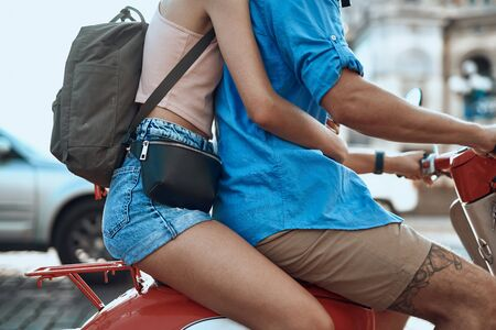 Lady with backpack and waist pack sitting behind man on motorbike
