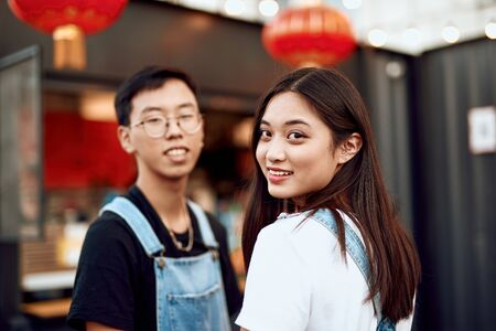 Asian couple staying together on street cafe view