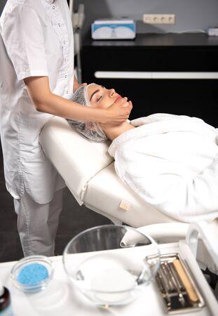 Masseuse massaging face of young woman at spa salon Stock Photo