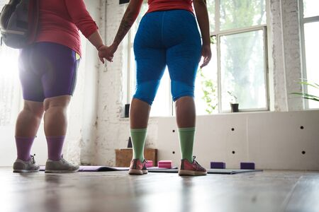Cropped photo of fat ladies going to work out in gym