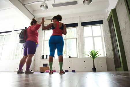 Two female friends are ready for sport exercises in gym