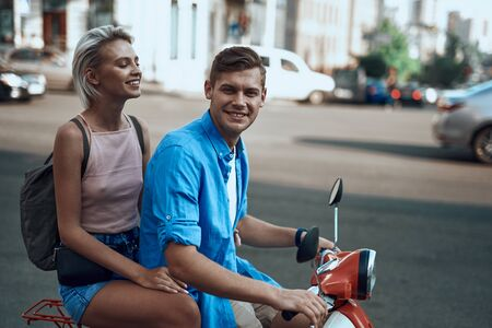 Happy young couple is riding the motorbike Stock Photo