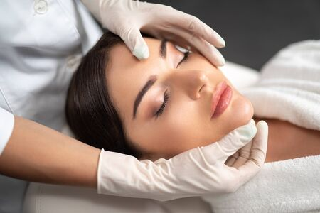 Young woman receiving face lifting massage at beauty salon Stock Photo
