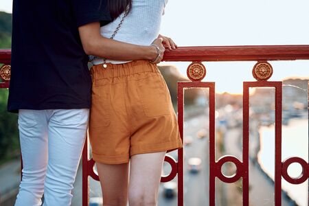 Beloved stylish young couple embracing on bridge