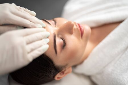 Beautiful young woman is receiving face massage Stock Photo
