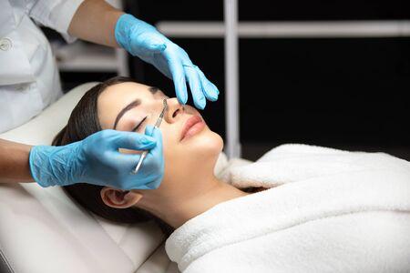Cosmetóloga eliminando las impurezas de la cara de la dama con removedor de espinillas